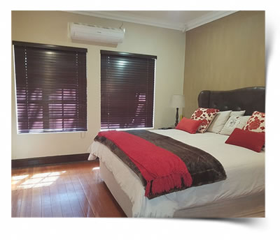 Two Basswood dark mahogany colour blinds blends in with bedding and wooden flooring of this bedroom in Bayswater Bloemfontein.